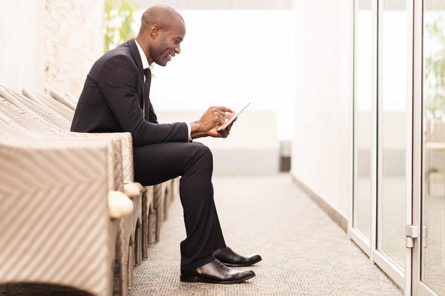 happy man looking at phone while sitting in lobby waiting area