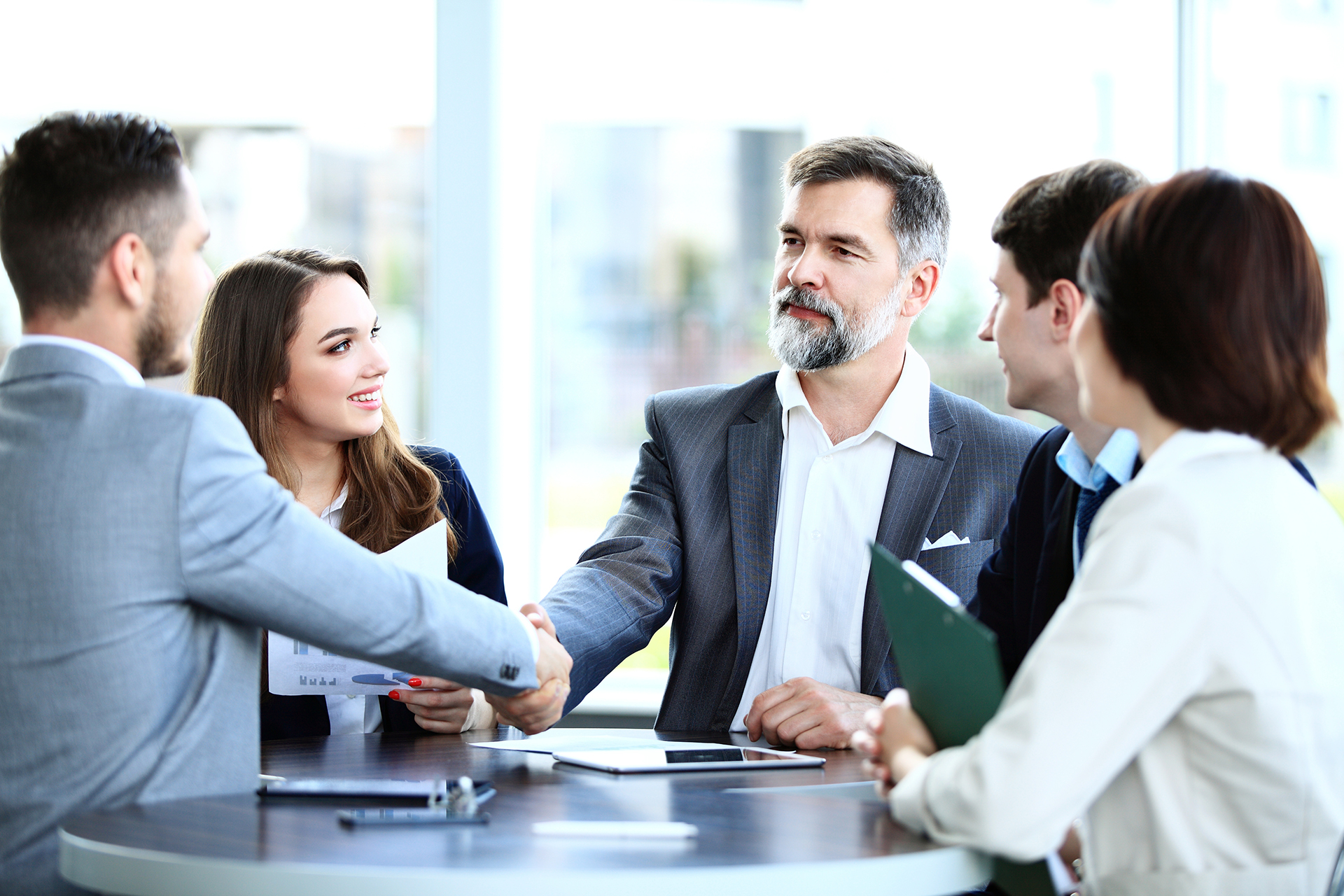 business team having friendly handshake over table at a meeting