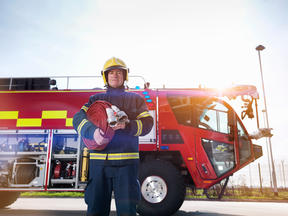 firefighter in uniform holding a hose standing in front of fire engine